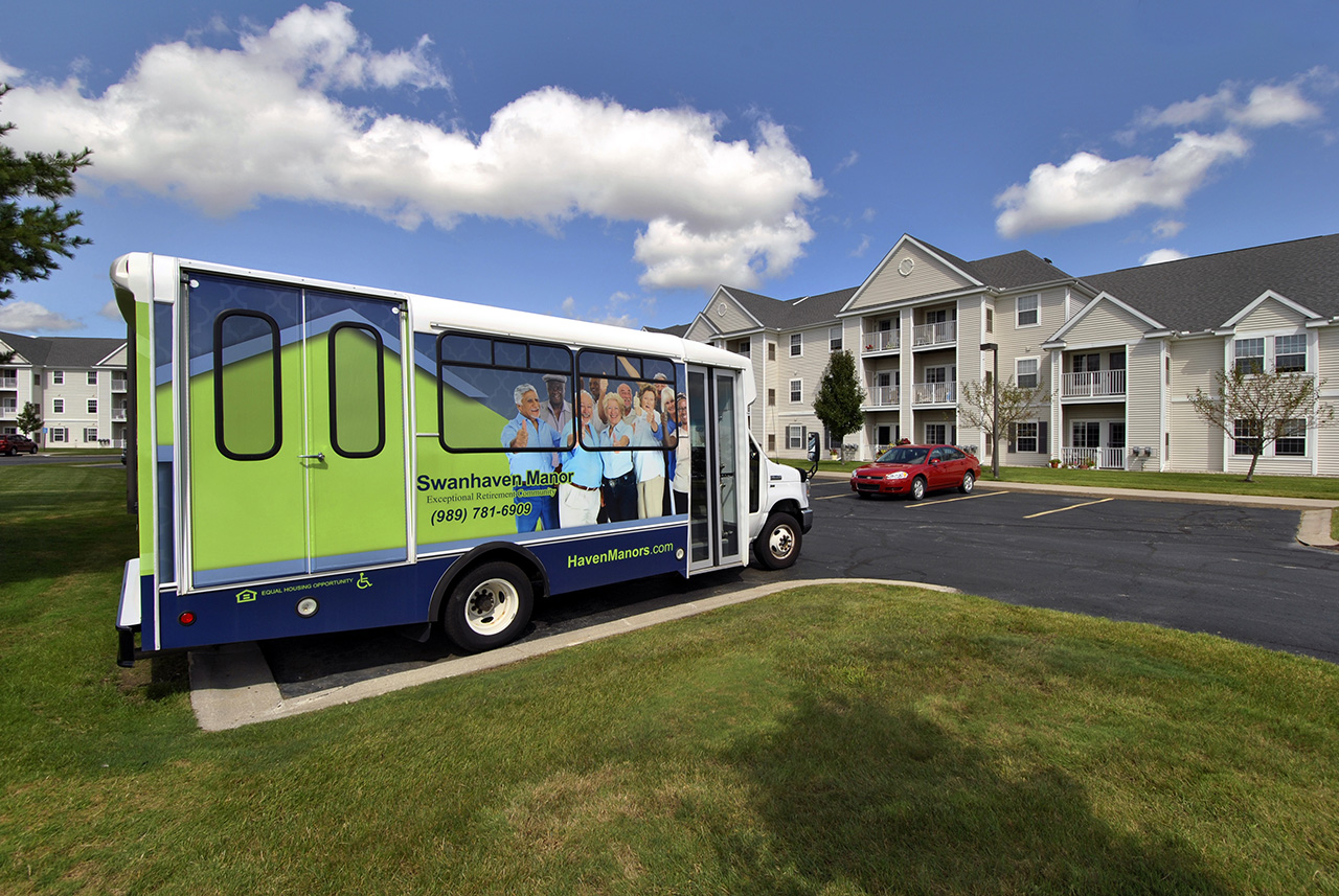 Swanhaven Manor bus in parking lot outside building